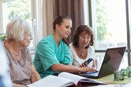 Nurse with senior women buying medicine online using laptop and credit card at nursing home - MASF11149