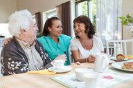 Young caregiver with senior couple during breakfast at nursing home - MASF11152