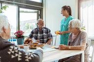 Smiling senior man and nurse talking while having breakfast at nursing home - MASF11158