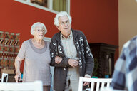 Senior couple standing arm in arm at nursing home - MASF11167