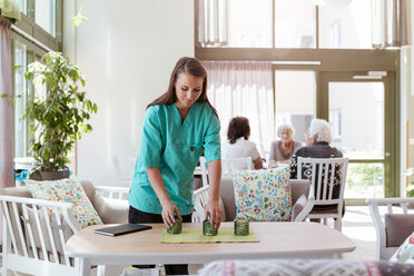 Female caretaker arranging table with senior people in background at nursing home - MASF11170
