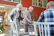 Senior man pulling chair out for woman in nursing home - MASF11173