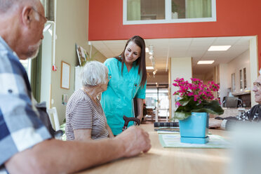 Smiling caregiver assisting senior woman sitting with friends at nursing home - MASF11176