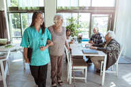 Young nurse and senior woman walking arm in arm at nursing home - MASF11179