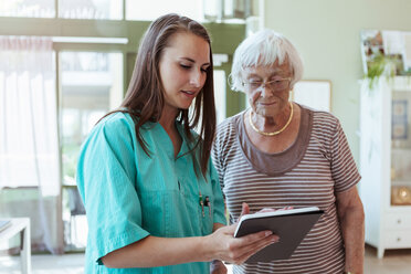 Female healthcare worker showing digital table to senior woman in nursing home - MASF11182