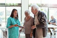 Young caretaker showing digital tablet to senior couple at nursing home - MASF11191