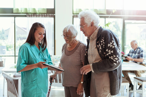 Young caretaker showing digital tablet to senior couple at nursing home - MASF11191