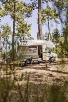 France, Gironde, woman sitting in front of camper on a camping ground using digital tablet - JATF01133