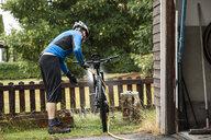 Mature man washing mountain bike in yard - MASF11203