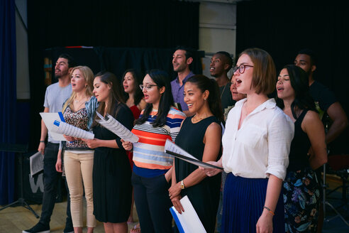 Multi-ethnic male and female students singing in choir at auditorium - MASF11233