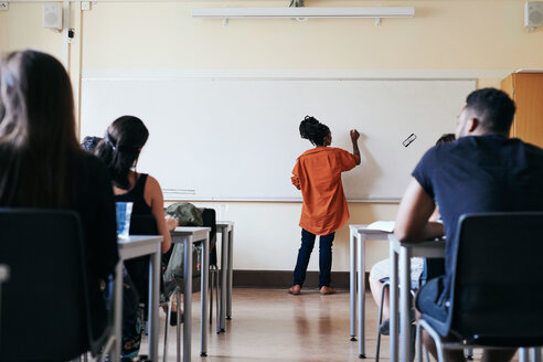 Rear view of female teacher writing on whiteboard in classroom - MASF11251