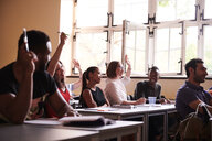 Intelligent students raising arms to answer in classroom - MASF11266