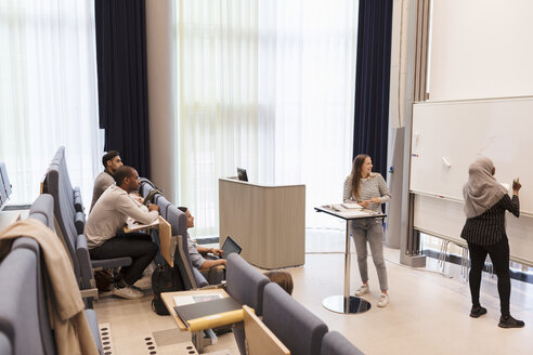 Students looking at friend writing on whiteboard during rehearsal in lecture hall - MASF11293