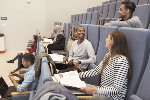 Smiling friends talking while studying at auditorium in university - MASF11296