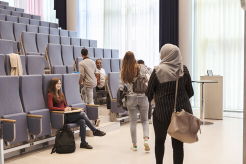 Smiling students looking at friends walking towards chairs in lecture hall at high school - MASF11299