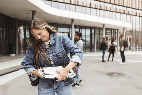 Smiling young woman holding books while standing in university campus - MASF11320