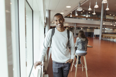 Portrait of smiling young student with backpack standing at university cafeteria with friend in background - MASF11347