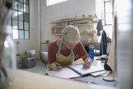 Female potter sketching in notebook at desk in art studio - HEROF22682