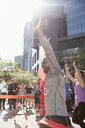 Exuberant male marathon runner crossing finish line with arms raised - HEROF22700