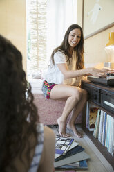 Female friends listening to music, playing vinyl records on record player in living room - HEROF22706