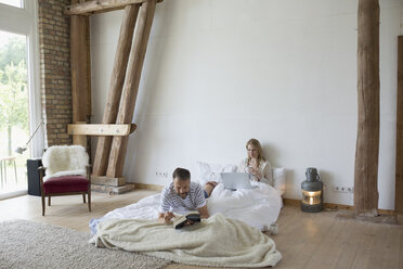 Couple reading and using laptop on bed mattress on cabin floor - HEROF22712