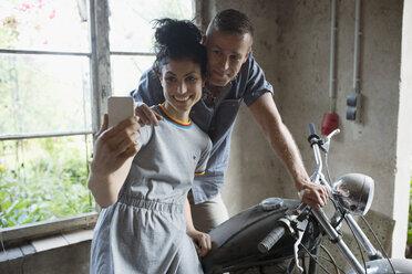 Couple taking selfie with camera phone on motorcycle in garage - HEROF22715