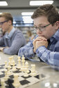 Focused male middle school student playing chess in chess club - HEROF22811