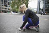 Female runner tying shoelace on urban street - HEROF22847