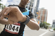 Male marathon runner checking smart watch on urban street - HEROF22853