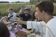 Friends drinking red wine and eating, enjoying garden party dinner - HEROF22883