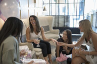 Laughing bride-to-be showing wedding ring to bridesmaid friends celebrating bridal shower in nail salon - HEROF22910