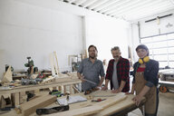 Portrait confident carpenters at workbench in workshop - HEROF22943