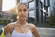 Portrait serious young female runner listening to music with earbud headphones and mp3 player arm band - HEROF22961