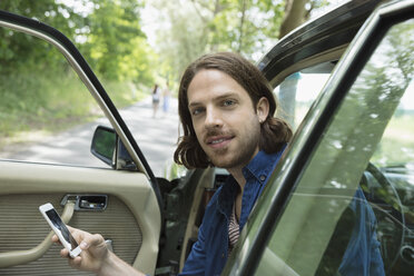 Portrait brunette man texting with cell phone in driver seat of car - HEROF22967