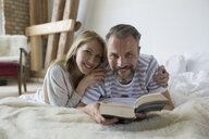 Portrait smiling couple reading book on bed - HEROF22976
