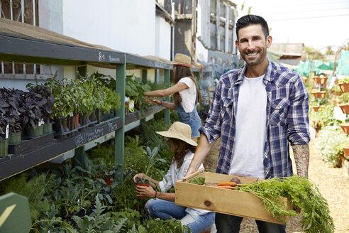 Portrait smiling man carrying crate of fresh, organic vegetables - HEROF23015