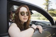 Portrait confident woman in sunglasses riding in car, enjoying road trip - HEROF23057