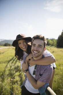 Portrait smiling affectionate young couple hugging in sunny summer rural field - HEROF23063