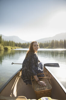 Portrait smiling woman with picnic basket and oar in canoe on sunny summer lake - HEROF23066