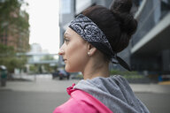 Pensive female runner wearing bandana on urban street - HEROF23099