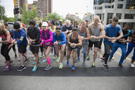 Marathon runners ready, preparing smart watches at starting line on urban street - HEROF23108