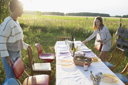 Mother and daughter setting the table for garden party dinner in rural summer yard - HEROF23141