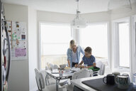 Mother helping pre-adolescent son doing homework at kitchen table - HEROF23159