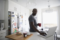 Mature African American man drinking coffee and using laptop at kitchen counter - HEROF23180