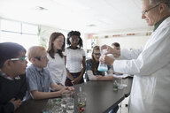 Teacher and middle school students conducting scientific experiment in science laboratory - HEROF23216