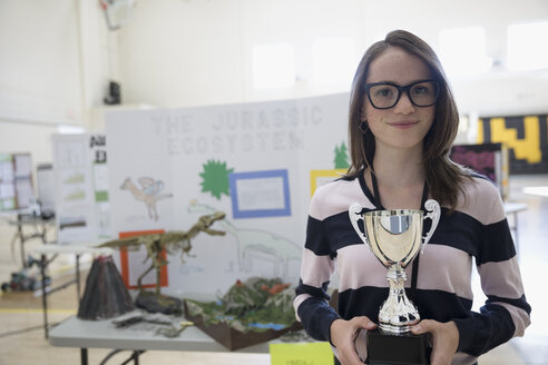 Portrait smiling, confident girl middle school student holding trophy at science fair - HEROF23225