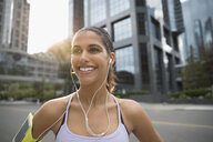 Portrait smiling, confident young female runner listening to music with earbud headphones and mp3 player - HEROF23234