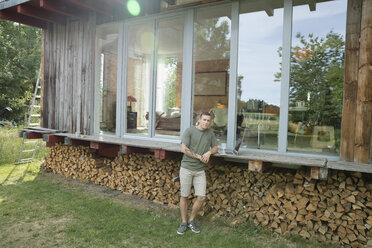 Portrait young man with laptop on wood cabin patio above firewood - HEROF23252
