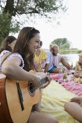 Smiling young woman playing guitar at summer picnic - HEROF23255