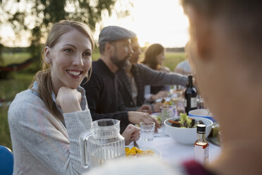 Smiling woman talking to friend, enjoying garden party dinner - HEROF23273